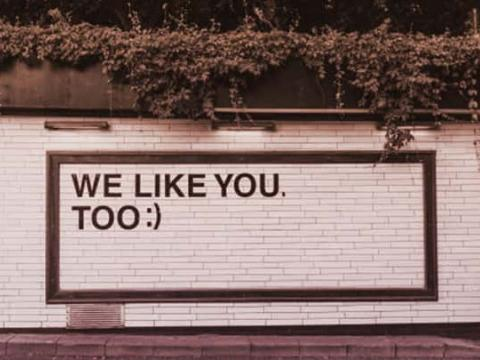 "The tiled side of a building with ""WE LIKE YOU. TOO :)"" in big letters on it"